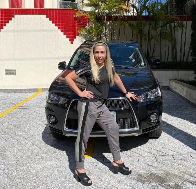 Mulher posando para foto em frente a carro  Descrição gerada automaticamente