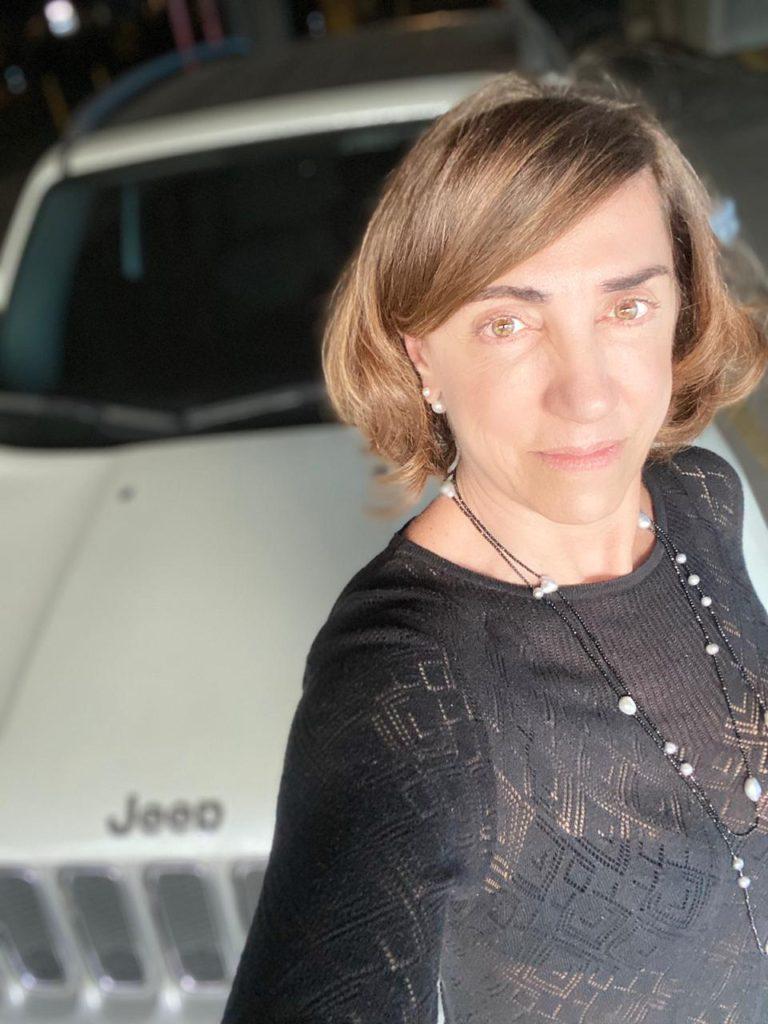 Mulher na frente de um carro  Descrição gerada automaticamente